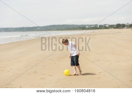 Ten year old boy playing football on the beach