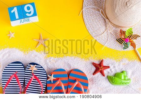 June 19th. Image of june 19 calendar on yellow sandy background with summer beach, traveler outfit and accessories. Summertime concept.