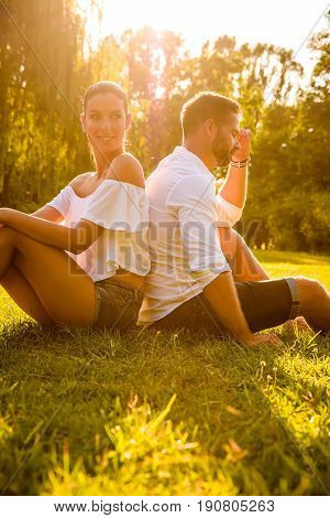 A beautiful young couple sitting back to back on a field in a park in the sunset