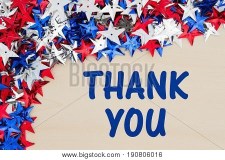 Thank You text with red white and blue stars on wood