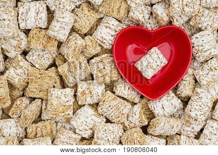 Whole grain wheat cereal with a red heart shaped bowl for a healthy cereal background
