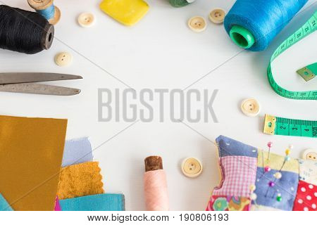 needlework, craft, sewing and tailoring concept - tools close-up on white desk, measuring meter, pink, blue and black thread spools, scraps of colorful fabric, pins and pincushion, white buttons, soap