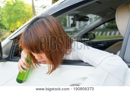 Drunk asian woman feels dizzy after too much drinking alcohol and driving car