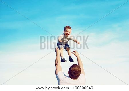 Happy Father Throws Son Child Into The Air, Carefree Having Fun Outdoors Over The Blue Sky Backgroun