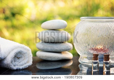 A spa treatment set, massage stones, a towel and massage oil are placed on a polished granite table in the garden.