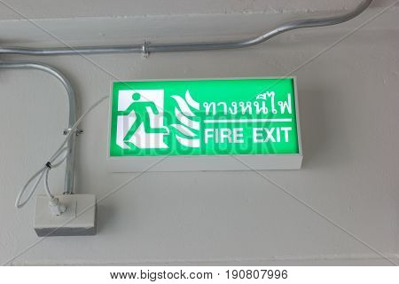 fire exit sign on the ceiling with Thai language