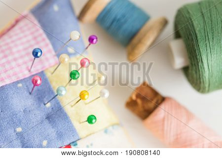 needlework, craft, sewing and tailoring concept - macro with beautiful stitched pincushion and colorful pins, pink, blue and green thread spools, white background, selective focus