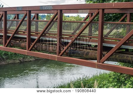 A rusted metal bridge spans the Green River in Kent Washington.
