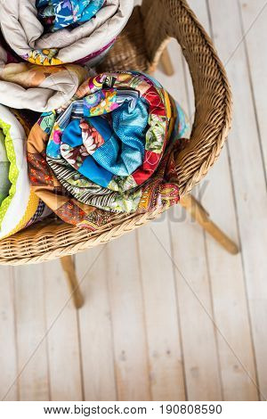patchwork and fashion concept - close-up on three colorful quilts rolled into a tube and laid in a wicker chair, warehousing of finished products on a white background, top view, vertical
