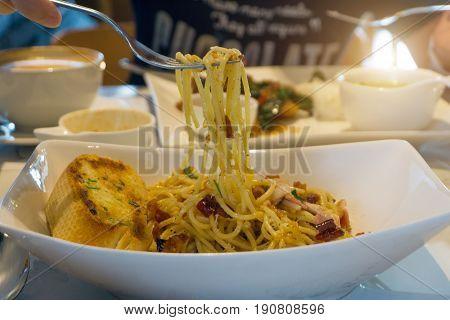 Fork Scooping Spaghetti Carbonara In Dish.