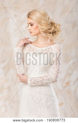 fashionable gown, beautiful blonde model, bride hairstyle and makeup concept - young exciting lady in white wedding festive dress, standing indoors on light background, romantic slender woman posing