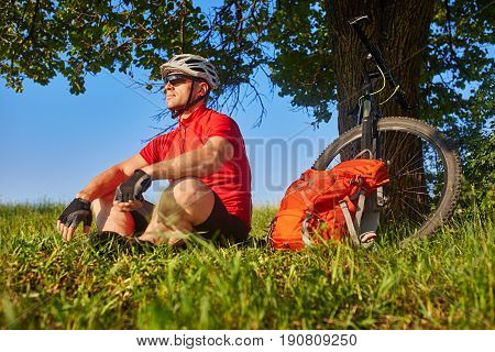 The attractive cyclist sitting on the grass near the bike and near the tree. Sportsman in the red t-shirt, black shorts, sportive shoes, with helmet and sunglasses. Beautiful landscape. Concept of the healthy lifestyle.