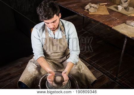 potter, workshop, ceramics art concept - young man working on potter's wheel with raw fireclay with hands, a male sculpts a utensil near wooden table with tools, master in apron and shirt, top view
