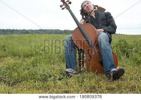 Musician with a happy look on his face having a break while performing a cello in a field landscape