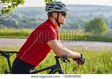 Portrait of athletic man standing with mountain bike against road in the countryside. Cyclist in the sportwear, with helmet and sunglasses. Extreme travel in the countryside. Concept of the healthy and active lifestyle.