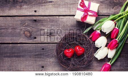 Decorative red little hearts in nest bright spring tulips flowers box with present on textured background. Selective focus. Place for text. Toned image.