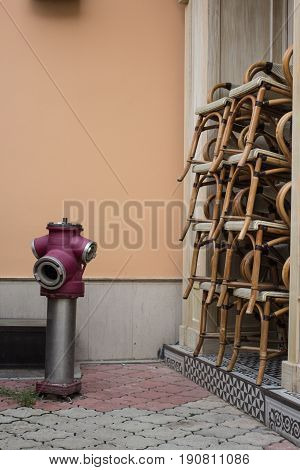 fire hydrant near closed cafe restaurant with stocked chairs waiting for visitors