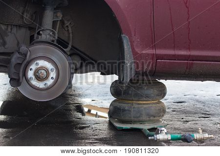 Car lift up by hydraulic waiting for tyre wheel replacement at repair service mounting road assistance