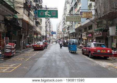 KOWLOON HONG KONG - APRIL 21 2017: Neons and Parked Taxis at Street Mong Kok in Kowloon Hong Kong.