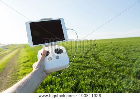 quadcopter flights outdoors, aerial imagery and tech hobby, recreation concept - white drone remote control in the man's hand of pilot on the background of green grass field and blue sky