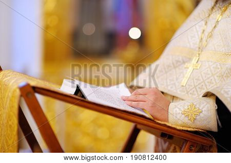 Close-up photo of Orthodox christian priest reading church book