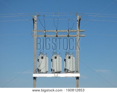 Three power transformers  along a transmission power line.