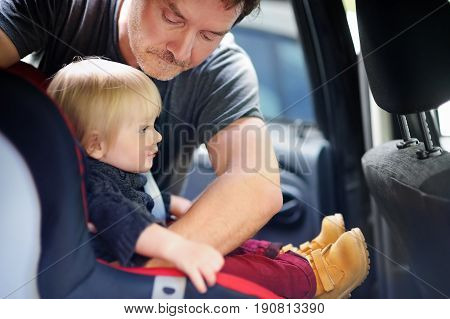 Middle age father helps his toddler son to fasten belt on car seat focus on father