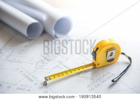 architectural drawing plan of house project blueprint rolls and yellow tape measure (measuring tape) on work table building construction industry concepts