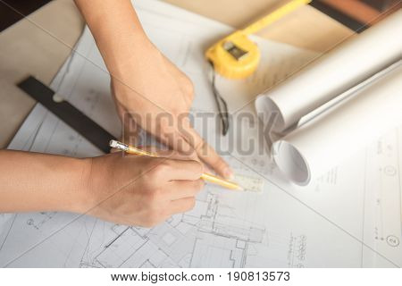 Architect male hands sketching on architectural drawing plan by using pencil and scale ruler design studio and building construction project concepts