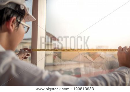 Young Asian engineer man using tape measure (measuring tape) on window frame at construction site Length measurement tool or equipment for building construction working