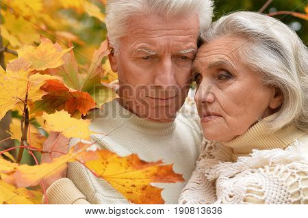 Portrait of sad senior couple hugging outdoors