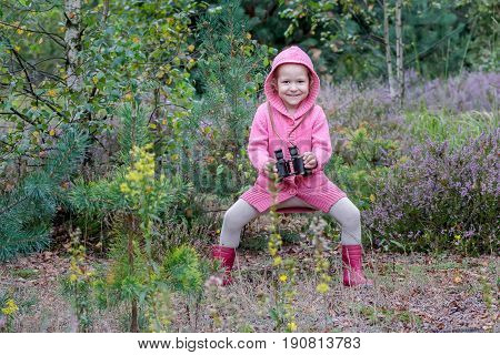 Excited little girl is jumping with binoculars in hand