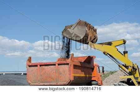 Wheel excavator on gravel pile loading a truck