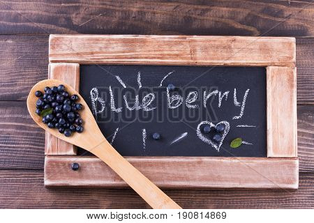 Blueberries in a wooden spoon on a vintage wooden table with black chalkboard. Bilberry on wooden Background. Blueberry antioxidant. Concept for healthy eating and nutrition
