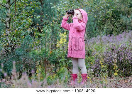 Little girl with binoculars is birdwatching in summer forest
