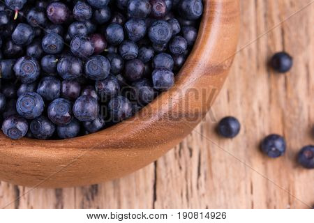 Blueberries in a bowl on a vintage wooden table. Bilberry on wooden Background. Blueberry antioxidant. Concept for healthy eating and nutrition