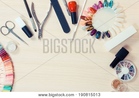 Manicure set on a wooden table. Nail files paints scissors nail accessories on pink bright background