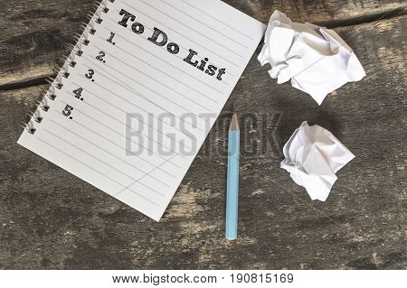 To Do List on a notebook with pen crumpled paper on wooden table. business concept.
