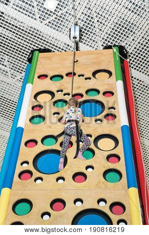 Little girl climbs to the top of the climbing wall, tied with a safety rope