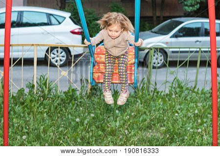Little girl is swinging on a swing on a playground in the courtyard of the house