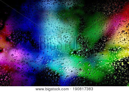 Abstract background of laser show in modern disco party night club : Concept of nightlife with music and entertainment. Rain drops on the glass. The selected focus.
