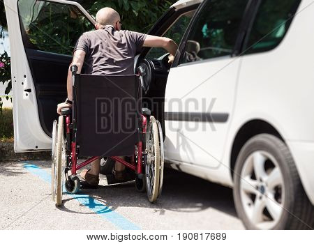adult male driver in wheelchair getting into the car