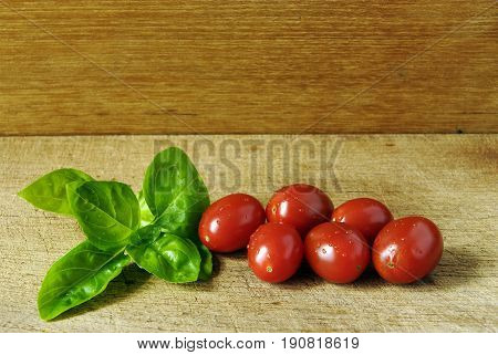 Grape tomatoes and a leafe of basil on a wooden plate