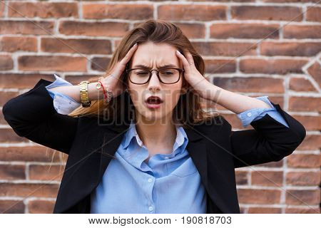 Terrible headache. Portrait of looking tired business woman in smart casual wear touching her head with hands