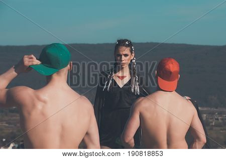 bandit girl or pretty woman with triangle painting on skin and stylish long brunette hair braids on mountain landscape. Two athletic men in red and green caps with naked backs. Sport and training
