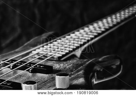 Close-up volume control of bass guitar. Black and white toning.