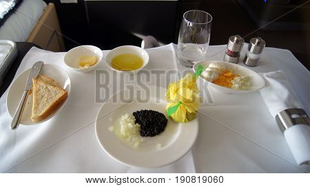 FRANKFURT, GERMANY - SEPTEMBER 2014: Traveling Lufthansa First Class in a Boeing 747-400 Upper Deck - Service with black caviar, Toast, onions and eggs.