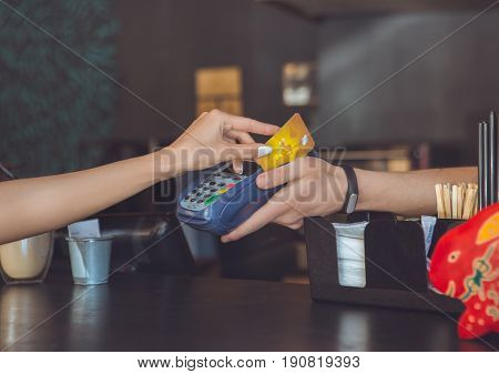 Young female sitting in a cafe indoors rest cashless payment