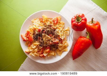 farfalle with tomato and paprika on green