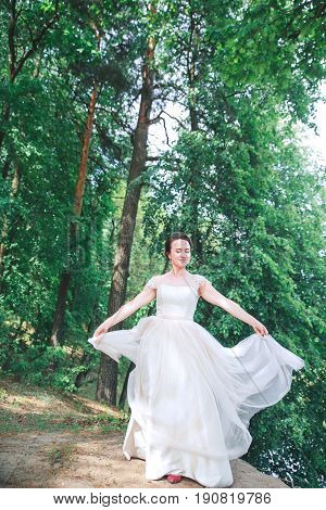 Beautiful bride in vintage white dress walking in the park. Gorgeous stylish bride
